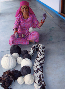 A picture of a woman in India holding yarn. She is one of the people who has benefitted from Knit for Peace projects around the world.