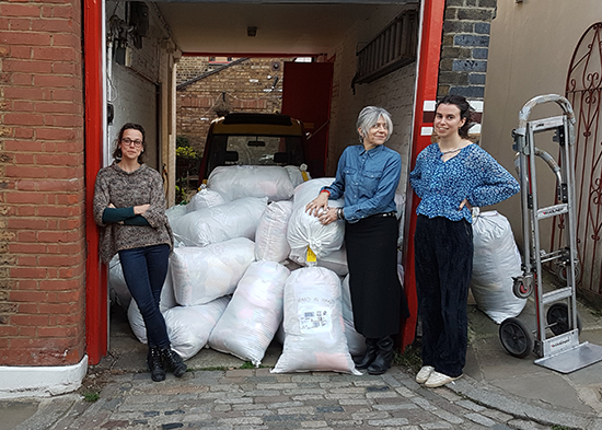 A picture of Knit for Peace staff waiting to load sacks of donated knitting to be sent to people in need.