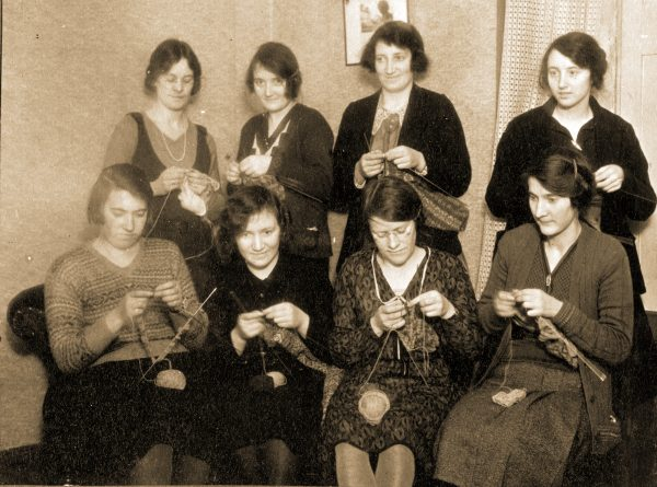 A rectangular Christmas card with a black and white picture of a group of women knitting.