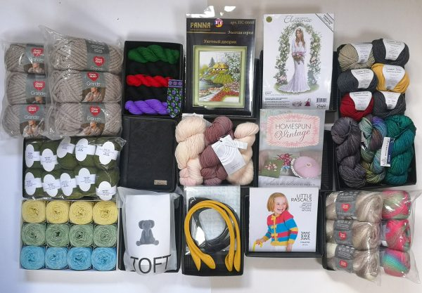 A picture taken from above of a variety of the potential prize you could receive in the Knit for Peace Lucky Dip: yarn, knitting supplies, embroidery kits and other crafting materials.
